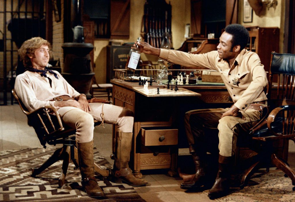 Full shot of Cleavon Little as Bart offering whiskey bottle for Gene Wilder as Jim, both seated in sheriff's office. PHOTOGRAPHS TO BE USED SOLELY FOR ADVERTISING, PROMOTION, PUBLICITY OR REVIEWS OF THIS SPECIFIC MOTION PICTURE AND TO REMAIN THE PROPERTY OF THE STUDIO. NOT FOR SALE OR REDISTRIBUTION. ALL RIGHTS RESERVED.